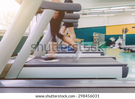 Closeup of people legs in motion during a treadmill training session on fitness center - stock photo