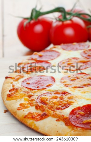 Closeup of pepperoni pizza, on a wooden board with ripe, juicy tomatoes in the background.  Shallow depth of field. - stock photo