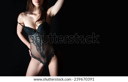 Closeup of perfect female body in black lingerie, studio shot in front of black background, photo with copy space on the right side of the image - stock photo