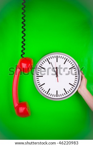 Closeup of person touching large clock next to dangling red retro style telephone, green background.