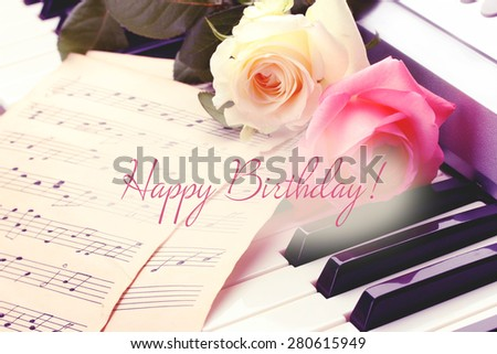 Closeup of piano keyboard with roses - stock photo