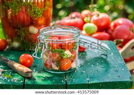 Closeup of pickled tomatoes in summer - stock photo