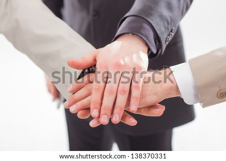 Closeup of pile of hands of business team showing unity. On white background. - stock photo