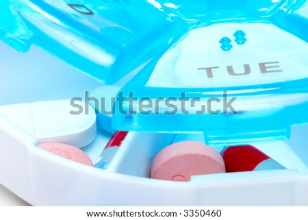 Closeup of pills planner with weekly amount of medication capsules in it - stock photo