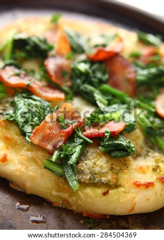 Closeup of pizza topped with bacon and greens - stock photo