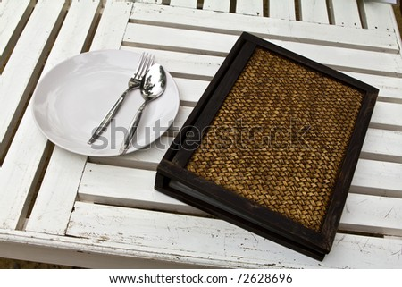 closeup of plate and wooden menu on old white wood table - stock photo