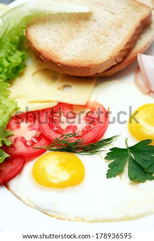Closeup of plate with fried eggs and tomatoes near bread