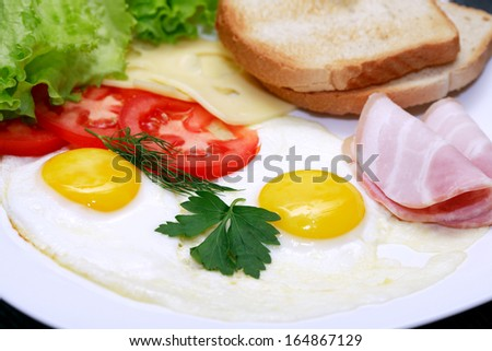 Closeup of plate with fried eggs, toasts and cheese