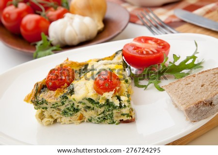 Closeup of plate with one piece of fresh made frittata, bread, and tomatoes. Pan with frittata with baby kale, sundried tomatoes, and goat cheese in background.  - stock photo