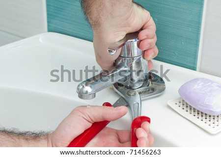 Closeup of plumber hands using wrench pliers to tight the water outlet - stock photo