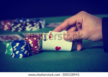 Closeup of poker player with two aces in pastel colors - stock photo