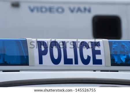 Closeup of police car sign with video unit vehicle in background. - stock photo