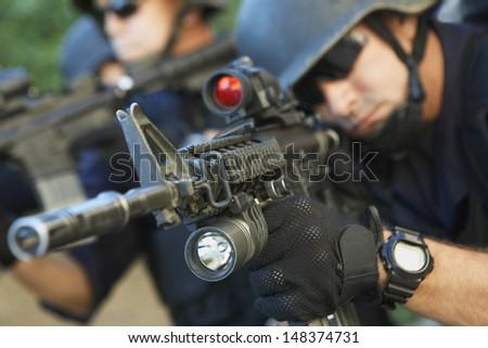 Closeup of policeman aiming guns - stock photo