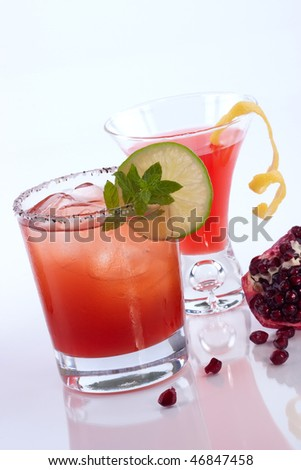 Closeup of Pomegranate Mojito, Pomegranate martini and broken open pomegranate over white. Vodka, rum, pomegranates juice, lemon, lime and mint. Most popular cocktails series. - stock photo