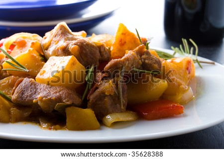 Closeup of pork stew with potatoes on a white plate