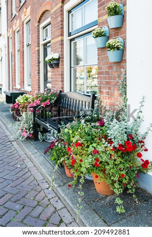 Closeup of pots with colorful flowering plants in a street in the Dutch village of Middelharnis - stock photo