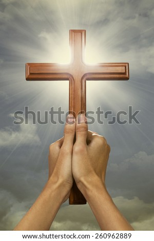Closeup of prayer hands holding a cross wood and raising the cross to the sky - stock photo