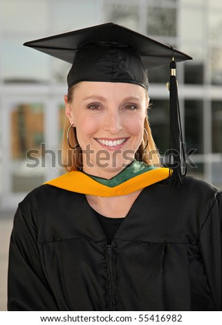 closeup of pretty blond female graduate woman in cap and gown in front of college building