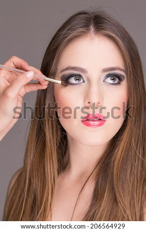 closeup of pretty blond young woman getting makeup done looking up - stock photo