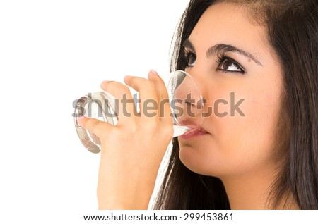 closeup of pretty latin girl drinking water from a glass isolated on white - stock photo