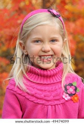 closeup of pretty little blond girl outdoors in autumn - stock photo