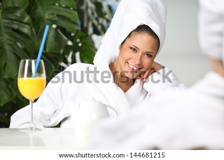 Closeup of pretty smiling woman with juice glass outdoors - stock photo