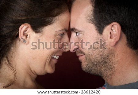 Closeup of pretty woman and handsome man touching noses - stock photo