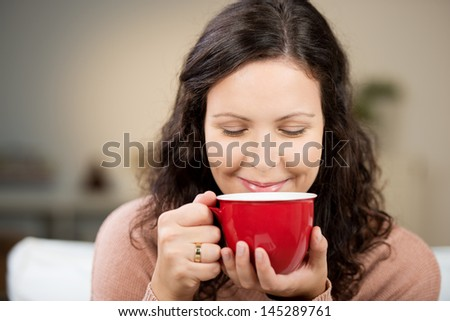 Closeup of pretty woman with eyes closed drinking coffee at home - stock photo