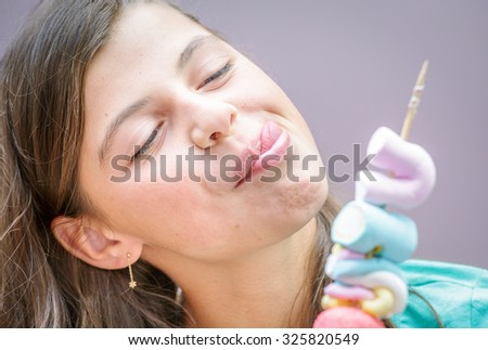 closeup of pretty young girl eating a delicious marshmallow skewer