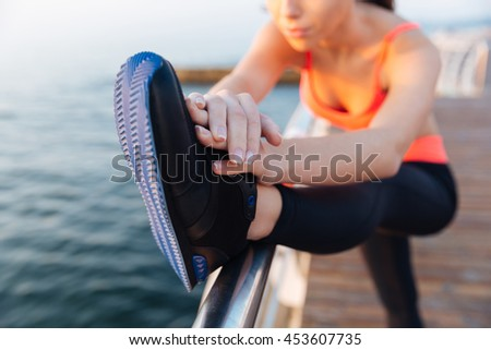 Closeup of pretty young sportswoman working out and stretching legs outdoors - stock photo
