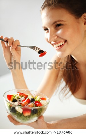 Closeup of pretty young woman eating vegetable salad - stock photo