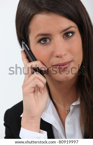 Closeup of pretty young woman in a suit on cellphone - stock photo