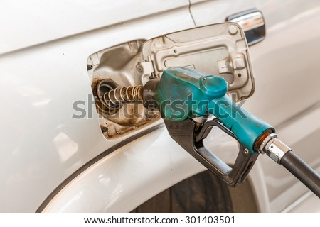 Closeup of pumping gasoline fuel into car tank - stock photo