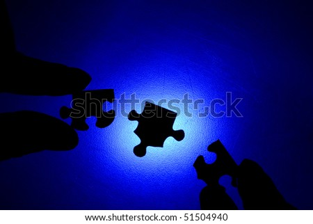 Closeup of puzzle pieces sihouetted against blue background - stock photo
