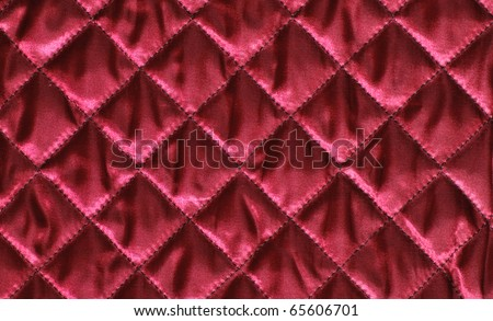 Closeup of quilted red satin fabric - stock photo