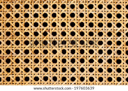 Closeup of rattan weave isolated on black background - stock photo