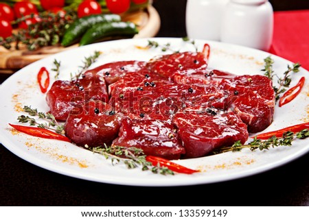 Closeup of raw beef medallions served on plate with rosemary, pepper and spices - stock photo