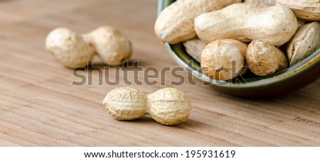 Closeup of raw peanuts scattered on wooden board, and in a bowl.