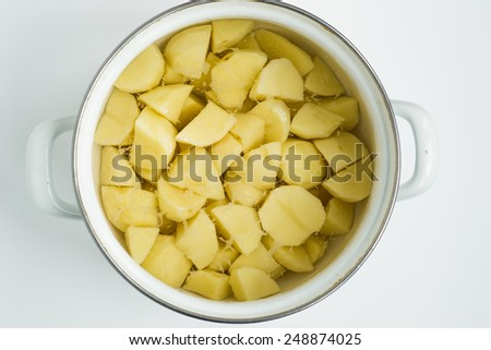 Closeup of raw peeled potatoes in pot on white background - stock photo
