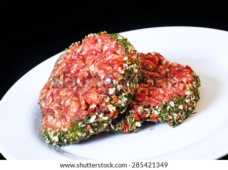Closeup of raw red hamburgers on white plate isolated on black - stock photo