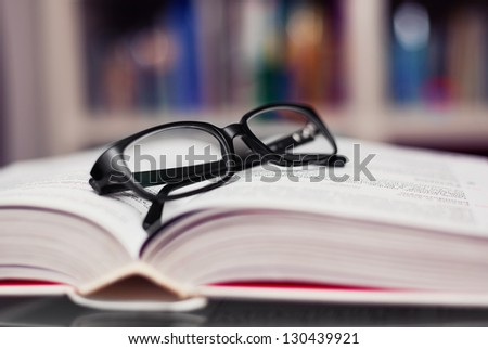 Closeup of reading glasses on the book. - stock photo