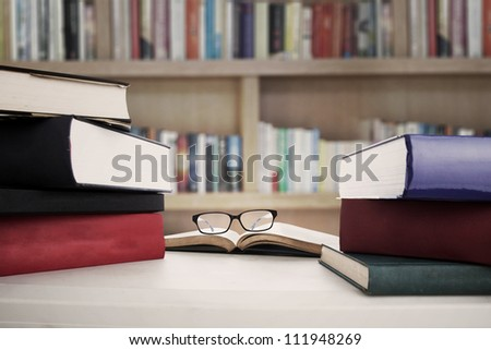 Closeup of reading glasses on the book between stack of textbooks. shot in the library - stock photo