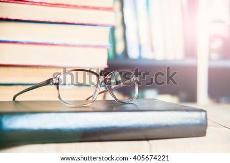Closeup of reading glasses on the book, pile of books - stock photo
