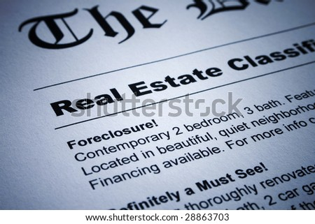 Closeup of real estate classified ads on newspaper - stock photo