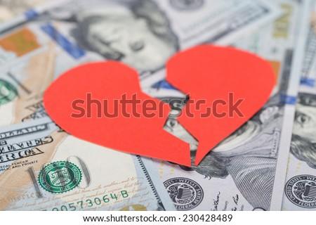 Closeup of red broken heart on dollar bills - stock photo