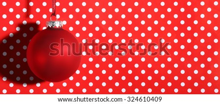 Closeup of red Christmas ball on festive background - stock photo