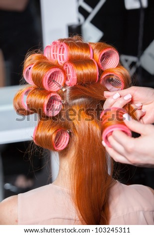 Closeup of red hair during hair dressing with curler - stock photo