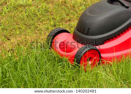 Closeup of  red lawnmower mowing the grass - stock photo