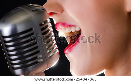 Closeup of red lips singing into retro microphone