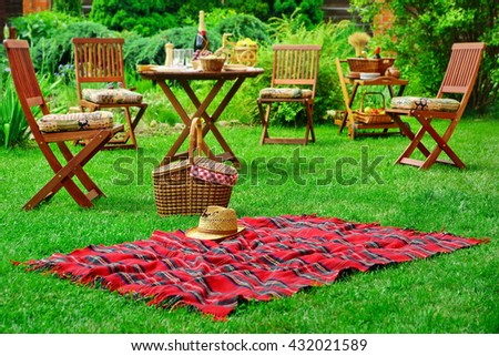 Closeup Of Red Picnic Blanket With Straw Hat And Basket Or Hamper. Blurred Outdoor Wooden Furniture In The Background. Family Home Backyard Party Or Picnic Conceptual Scene - stock photo